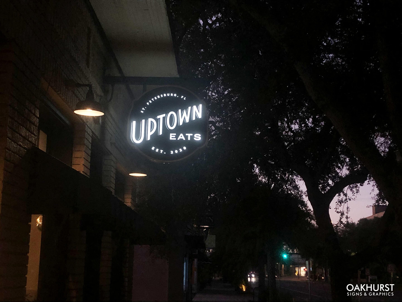 Retail blade sign lighting up at night
