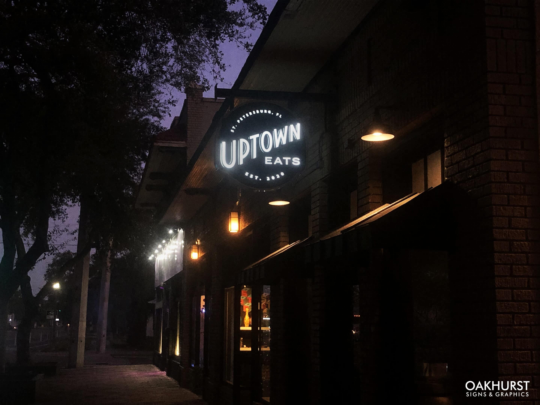 Uptown Eats blade sign in the dark